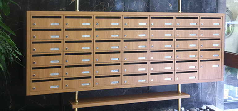 Boites aux lettres collectives en bois dans un hall d'entrée sur mur en marbre